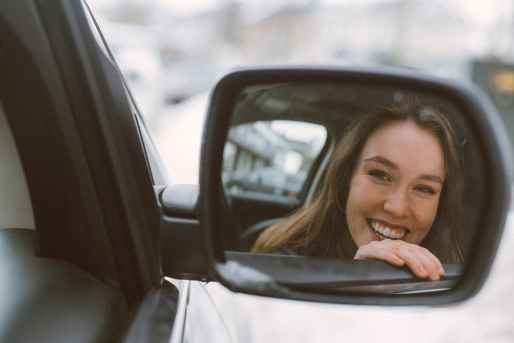 woman smiling refection on vehicle side mirror